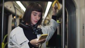 Ståenden av den unga hipsterkvinnan rymmer ledstången, genom att använda smartphonen som offentligt står transport stadslampor lager videofilmer