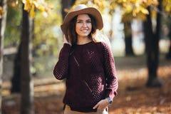 Ståenden av den unga kvinnan för det lyckliga leendet i höst parkerar utomhus i hemtrevlig tröja och hatt Varmt soligt väder Nedg arkivfoto