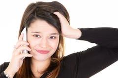 Ståenden av den unga kvinnan med en telefon är egentligen förargat frustrerat arkivbild