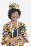 Ståenden av den unga kvinnliga modeformgivaren i afrikanska händer för tryckdressanseende vek över grå bakgrund arkivbilder