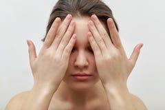Ståenden av den unga kvinnliga modellen som stänger henne ögon med henne, gömma i handflatan och att göra ansikts- massage Royaltyfria Foton