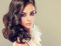Ståenden av den unga lockiga haired brunetten med livlig östlig stil utgör Eleganta lockiga frisyrer fotografering för bildbyråer