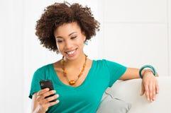 Ung kvinna som ser mobiltelefon Royaltyfria Bilder