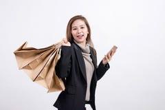 Ståenden av den unga lyckliga le asiatiska kvinnan med shoppingpåsar och ilar telefonen fotografering för bildbyråer