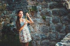 Ståenden av den unga romantiska kvinnan med långt hår, röda kanter och manikyr i den vita klänningen blommar Attraktiv flicka i S Royaltyfria Bilder
