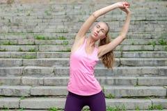 Ståenden av den unga sportiga kvinnan i sportklänning gör sträckning av utomhus- övningar royaltyfria bilder