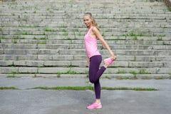 Ståenden av den unga sportiga kvinnan i sportklänning gör sträckning av utomhus- övningar arkivbilder