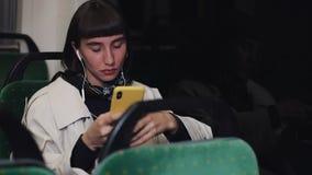 Ståenden av den unga stilfulla kvinnan i hörlurar som lyssnar till musik och bläddrar på mobiltelefonen transporterar offentligt  stock video