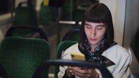 Ståenden av den unga stilfulla kvinnan som bläddrar på mobiltelefonen transporterar offentligt Ungt stads- yrkesmässigt lyckat stock video