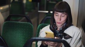Ståenden av den unga stilfulla kvinnan som bläddrar på mobiltelefonen transporterar offentligt Ungt stads- yrkesmässigt lyckat arkivfilmer