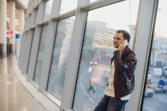 Ståenden av den unga stiliga personen som bär tillfällig stil, beklär det stående near fönstret i modern flygplatsterminal handel Royaltyfria Bilder