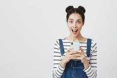 Ståenden av den upphetsade brunettstudentflickan som ser mobiltelefonskärmen i chock med sned boll, öppnade muninnehavtelefonen i Arkivfoton