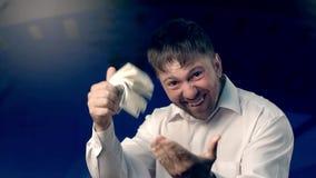 Ståenden av den upphetsade mannen som rymmer en stor packe av dollar och att vinka dem, och hans handlag gömma i handflatan med d lager videofilmer