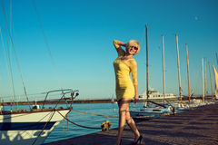 Ståenden av den ursnygga medelåldersa blonda le kvinnan som bär gult åtsittande-inpassat, snör åt klänningen och solglasögon som  Arkivbild