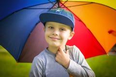 Ståenden av den vita pojken i ett lock med ett färgrikt paraply i en grön sommar parkerar lite på en solig dag fotografering för bildbyråer