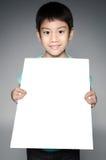 Ståenden av det asiatiska barnet med den tomma plattan för tillfogar din text. Arkivfoto