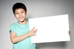 Ståenden av det asiatiska barnet med den tomma plattan för tillfogar din text. Arkivfoton