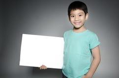 Ståenden av det asiatiska barnet med den tomma plattan för tillfogar din text Royaltyfri Foto