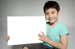 Ståenden av det asiatiska barnet med den tomma plattan för tillfogar din text Arkivfoton