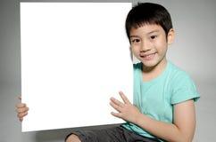 Ståenden av det asiatiska barnet med den tomma plattan för tillfogar din text Arkivbilder