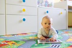 Ståenden av det gulliga lilla litet barnbarnet som spelar på minnestavlan, behandla som ett barn b Royaltyfri Foto