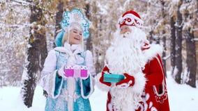Ståenden av det iklädda nya året för mannen och för kvinnan kostymerar hållande gåvor i händer