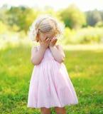 Ståenden av det lilla barnet stänger hennes framsida utomhus Arkivfoton
