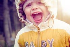 Ståenden av det lilla lyckliga barnet i huv och värme kläder i tidig vår Att skratta behandla som ett barn i natur Fotografering för Bildbyråer