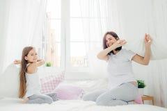 Ståenden av det lyckliga lilla barnet rymmer kudden, har kamp tillsammans royaltyfria bilder