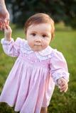 Ståenden av det lyckliga litet behandla som ett barn flickaställningar i parkera på gräset och rymmer hennes hand för moder` s Royaltyfri Bild