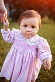 Ståenden av det lyckliga litet behandla som ett barn flickaställningar i parkera på gräset och rymmer hennes hand för moder` s Royaltyfri Fotografi