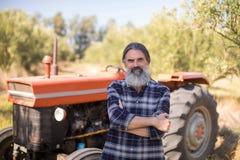 Ståenden av det lyckliga mananseendet med armar korsade mot traktoren Royaltyfri Bild