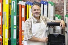Ståenden av det lyckliga mogna anseendet för lagerkontoristen vid mångfärgade stegar i maskinvara shoppar royaltyfria foton