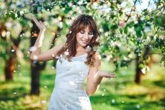 Ståenden av det unga le kvinnaanseendet under ett blomningträd och att se gömma i handflatan och fallande kronblad royaltyfria foton