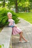 Ståenden av en blondin i rosa färger klär i en parkera utomhus fotografering för bildbyråer