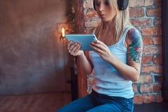 Ståenden av en blondin tattoed hipsterkvinnan som ser något på en digital minnestavla och en lyssnande musik, medan sitta på a Arkivfoto