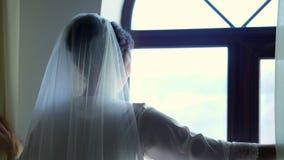 Ståenden av en brud, härlig flicka, i skyler, och vit peignoir, ämbetsdräkt, skjuter gardinerna, ser ut fönstret arkivfilmer