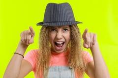 Ståenden av en emotionell le tonårig flicka i hatt som pekar på kameran som visar handgesten denna, är dig, över gul studio royaltyfria foton