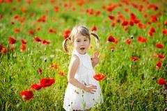 Ståenden av en förtjusande litet barnflicka förvånas i en vit klänninglek i ett härligt fält av röda vallmo arkivfoto