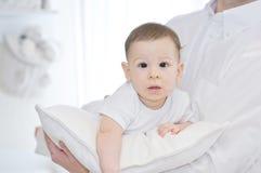 Ståenden av en fader med hans älskvärt behandla som ett barn pojken på den vita kudden Arkivfoto