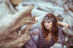 Ståenden av en flicka i en felik klänning sitter nära de gamla träden Arkivbilder