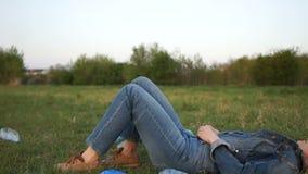 Ståenden av en flicka i en grov bomullstvilldräkt som ligger i mitt av plast- avfall på gräset i, parkerar stock video