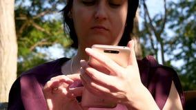 Ståenden av en flicka i parkerar som använder en smartphone för att meddela i sociala nätverk arkivfilmer