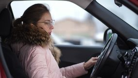 Ståenden av en flicka med exponeringsglas, som kör en bil, vänder går hon av bilen och ut 4K långsam Mo lager videofilmer
