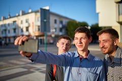 Ståenden av en grupp av att le och grinar vänner på sommarferie som gör selfie på kamera på stads- bakgrund royaltyfri fotografi