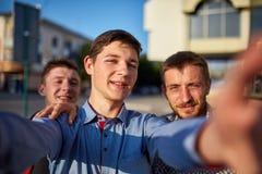 Ståenden av en grupp av att le och grinar vänner på sommarferie som gör selfie på kamera på stads- bakgrund royaltyfri foto