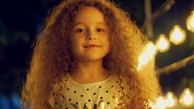 Ståenden av en gullig europeisk lockig-haired liten flicka ett barn ser kameran som sött ler mot bakgrunden lager videofilmer