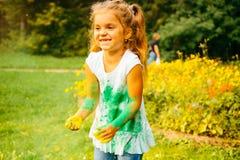 Ståenden av en gullig flicka målade i färgerna av den Holi festivalen royaltyfri foto