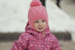 Ståenden av en gullig liten flicka som har gyckel i snö, parkerar arkivfoton