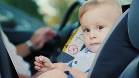 Ståenden av en gullig pyspojke, sitter i ett bilsäte för barn` s nära påven Säkerhets- och barnavårdbegrepp arkivfoton
